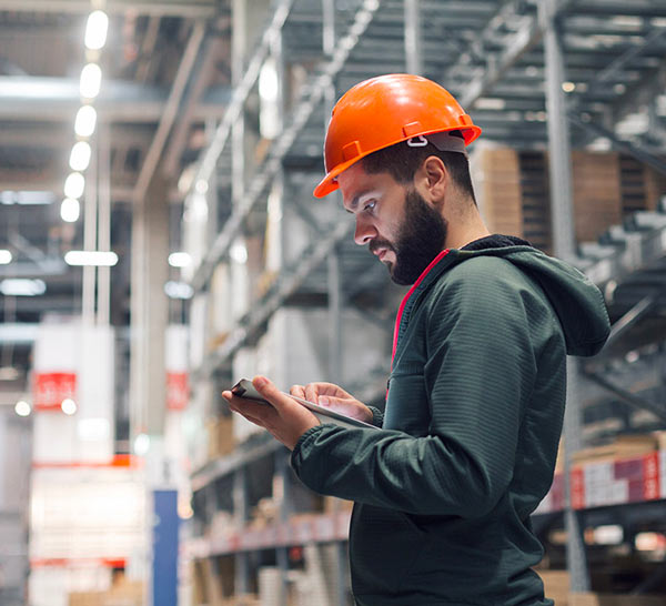 Worker in warehouse looking at tablet